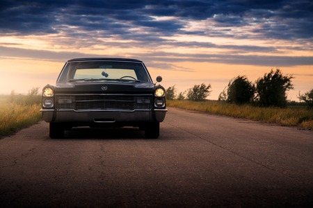 Engels, Russia - June 08, 2018: Black retro vintage muscle car Cadillac Fleetwood Brougham is parked at countryside asphalt road at golden sunset