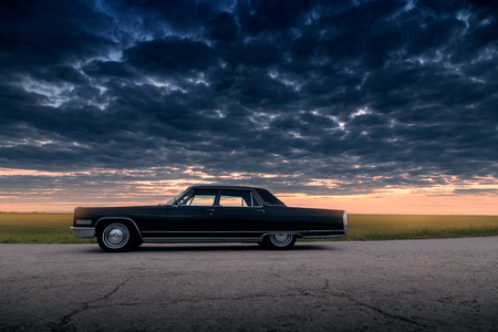 Engels, Russia - June 08, 2018: Black retro vintage muscle car Cadillac Fleetwood Brougham is parked at countryside asphalt road at dusk Editorial