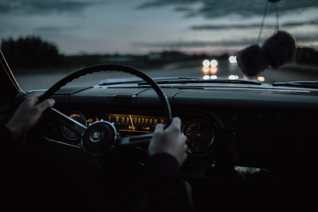 Engels, Russia - June 08, 2018: Black retro vintage muscle car Cadillac Fleetwood Brougham is driving at countryside asphalt road at dusk. View from interior Editorial