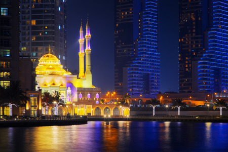 Beautiful view of Dubai Marina, UAE. Mohammed Bin Ahmed Almulla Mosque is illuminated at night. Long exposure time lapse effect