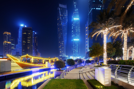 Beautiful view to Dubai Marina, UAE. Illuminated boat and palms. Long exposure time lapse effect at night