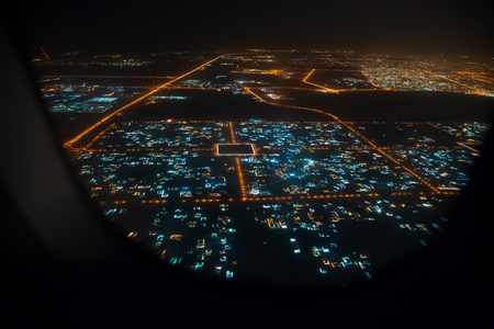Aerial view of Sharjah from airplane window at night, United Arab Emirates