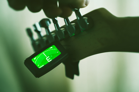 Tuning Electric Guitar With Chromatic Tuner. Shallow Depth Of Field 版權商用圖片