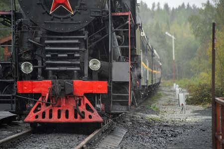 Old retro vintage steam train on platform station Ruskeala Park Фото со стока