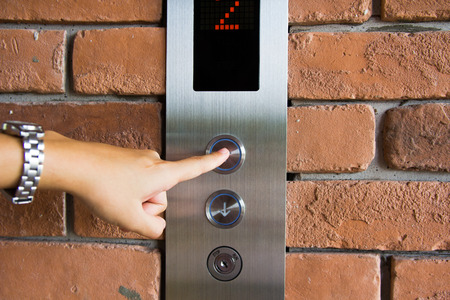 people  pressing elevator button photo