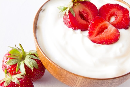 yogurt with strawberry in a wooden bowl photo