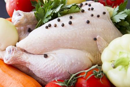 carne de pollo: Pollo crudo con pimienta y verduras listos para estar preparados