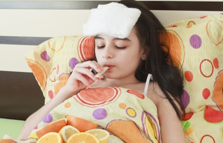 caucasian fever: young girl with a thermometer in bed