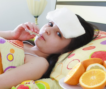 caucasian fever: Sick young girl with a thermometer in bed Stock Photo