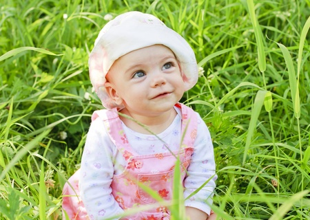 Happy baby girl with blue eyes lying on grass
