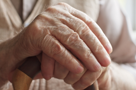hand of a senior man holding a cane