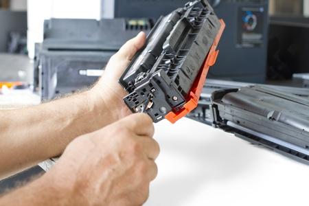 hands repairing laser toner cartridge