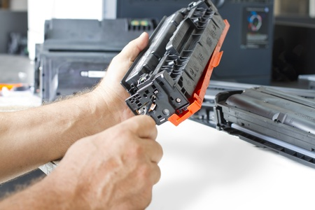 refill: hands repairing laser toner cartridge