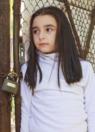petite fille triste: Triste et apeur�e petite fille en face d'une cl�ture en fil de Banque d'images
