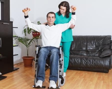 personas discapacitadas: Hombre joven que trabaja con un terapeuta físico