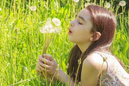 releasing: Little girl blowing dandelions, nine at the same time