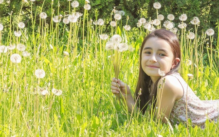 Little girl blowing dandelions, nine at the same time photo
