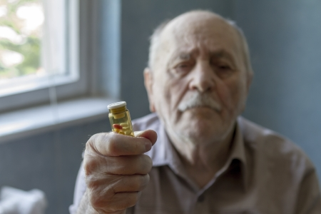 old man holding pills and he needs help photo