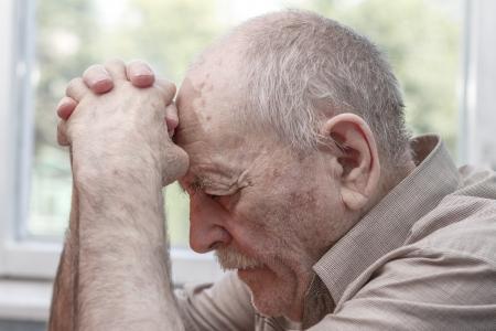 prayer hands: Uomo anziano che prega in casa vicino alla finestra