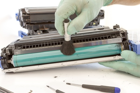 hands cleaning toner cartridge with brush the dust. worker Laser printer on a workbench. Printer workshop photo
