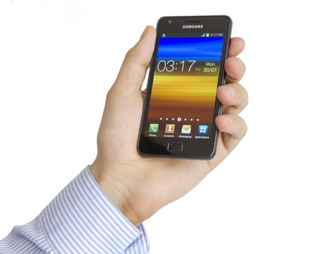 Galati, Romania – July 30, 2012: Hand holding the Samsung Galaxy S2. Samsung Galaxy S2 who has been sold in more than 20 million copies worldwide. Samsungs phone run the latest version of Android, Ice Cream Sandwich, the mobile operating system created by Editorial