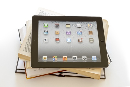 Ipad 3 on opened books on white background Editorial