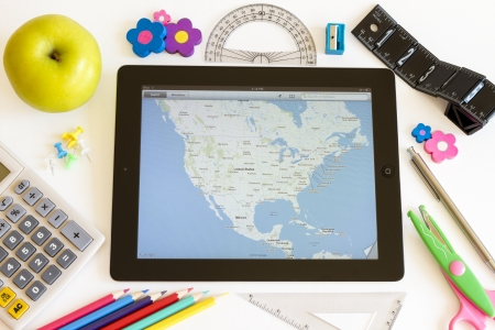 accesories: Ipad 3 with maps and school accesories on white background Editorial