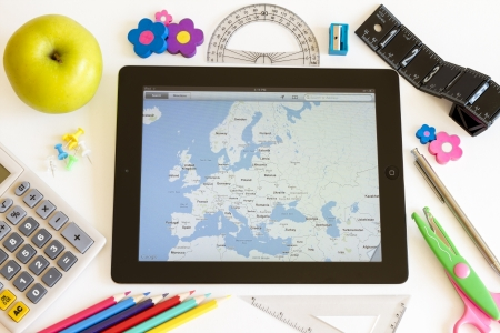Ipad 3 with maps and school accesories on white background