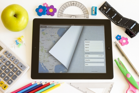 school things: Ipad 3 with maps and school accesories on white background Editorial