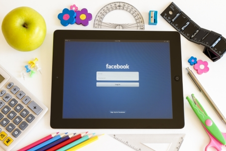 Facebook on Ipad 3 with school accesories on white background Editorial