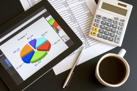 Modern workplace with digital tablet showing charts and diagram on screen, coffee, pen and paper with numbers  Standard-Bild