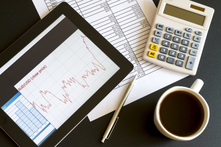 Modern workplace with digital tablet showing charts and diagram on screen, coffee, pen and paper with numbers Stock Photo - 16003531