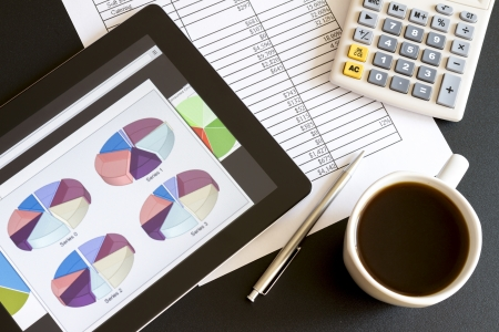 Modern workplace with digital tablet showing charts and diagram on screen, coffee, pen and paper with numbers  Stock Photo - 16003527