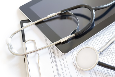 stethoscopes: Digital tablet with stethoscope and paperwork Stock Photo