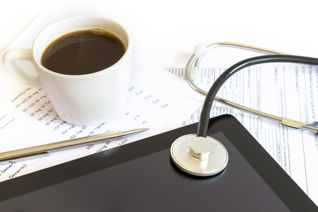 Digital tablet with stethoscope and paperwork photo