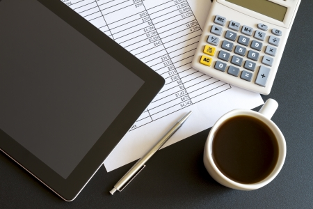 e market: Modern workplace with digital tablet showing charts and diagram on screen, coffee, pen and paper with numbers  Stock Photo