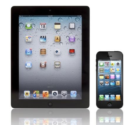 黒い Apple の iPhone 5 ブラック アップルのアプリ 3 タブレットの前に。両方のデバイスと同じ既定の壁紙ホームページを見せているし、白い反射表面