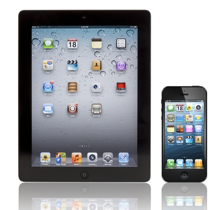 A black Apple iPhone 5 in front of a black Apple iPad 3 tablet. Both devices are showing the homepage with the same default wallpaper and are isolated on white on a reflective surface.