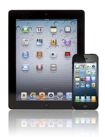 visual screen: black Apple iPhone 5 in front of a black Apple iPad 3 tablet. Both devices are showing the homepage with the same default wallpaper and are isolated on white on a reflective surface.