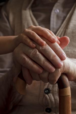 mano anziano: nipote mano che tiene le sue mani nonno