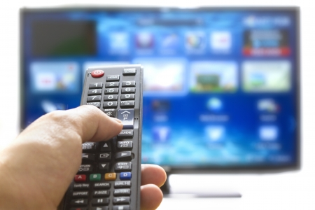 adjust: Television remote control changes channels thumb on the blue TV screen Stock Photo
