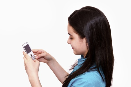 Teenage girl using smart phone on white background photo