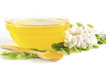 Honey in glass bowl and acacia on white background