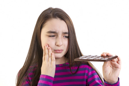 Girl child with toothache because his eats chocolate