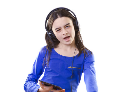 Smiling girl listening to music, holding a tablet pc in hands photo
