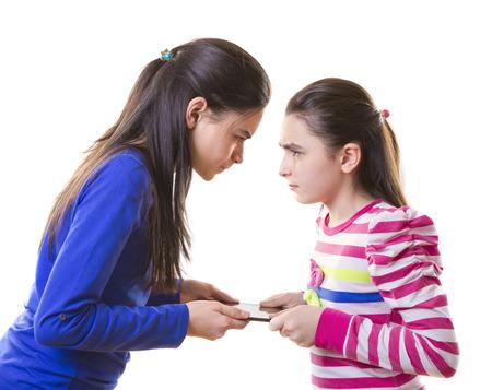 Teen girls Fighting for digital tablet  on white    photo