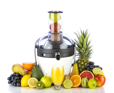 Fresh fruits and glass with juice near withe juicer on white background. Healthy fruits eating and drinking.