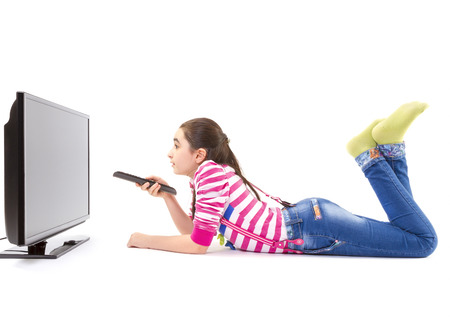 of down: Happy little girl laying down and watching tv Stock Photo