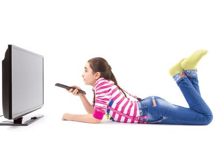 Niña feliz que se establecen y viendo la televisión