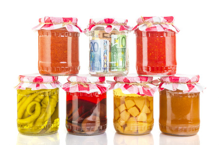 conserved: financial reserves money conserved in a glass jar among others preserves Stock Photo